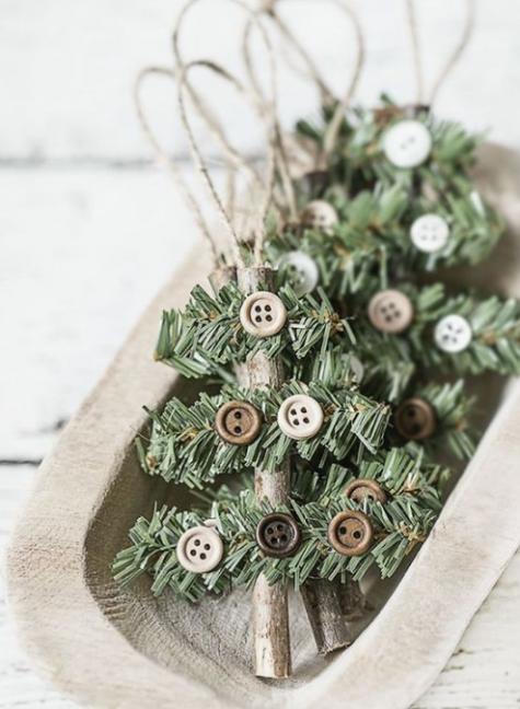 gli ornamenti natalizi rustici fatti di bastoncini, sempreverdi, bottoni e spago sono facili e alla moda per qualsiasi albero di Natale