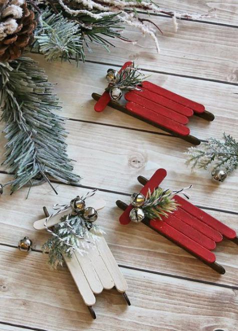 gli ornamenti natalizi rossi e bianchi di bastoncini di ghiaccioli con sempreverdi e campane daranno un tocco rustico e vintage