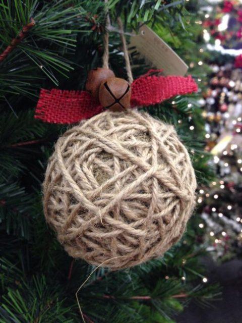 un ornamento di Natale avvolto in spago con tela rossa e campane di ruggine è una bella idea rustica con un accento accattivante