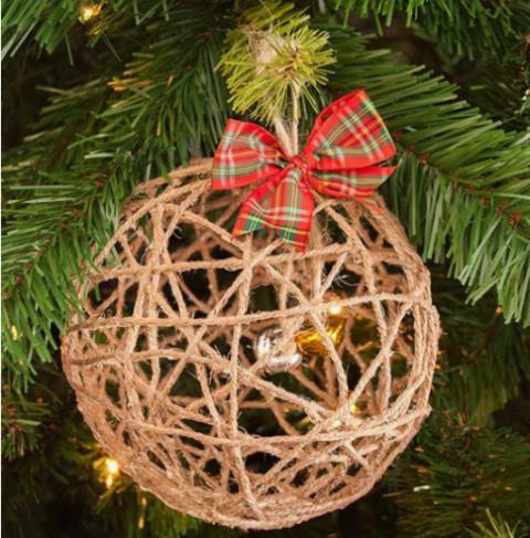 un ornamento di palla di Natale in filato con campane all'interno e un fiocco scozzese rosso in cima è un'idea carina e stravagante