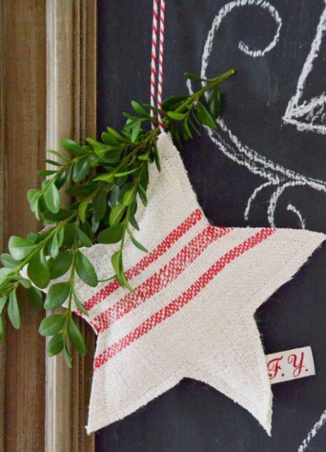 un ornamento a strisce rosse e bianche a stella di Natale con sempreverdi e spago rosso e bianco è un'idea tradizionale
