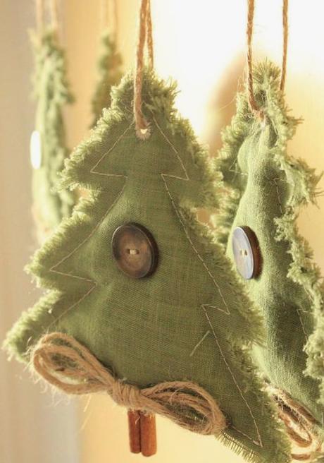 Gli addobbi per l'albero di Natale in tessuto verde, con grandi bottoni, spago e bastoncini di cannella sono un simpatico mestiere per le vacanze