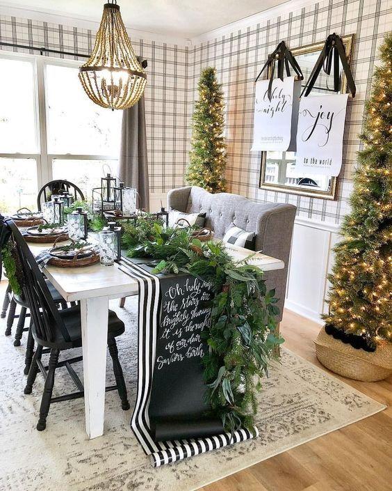 un'accogliente sala da pranzo in fattoria con alti alberi di Natale con luci è un'idea chic per le vacanze