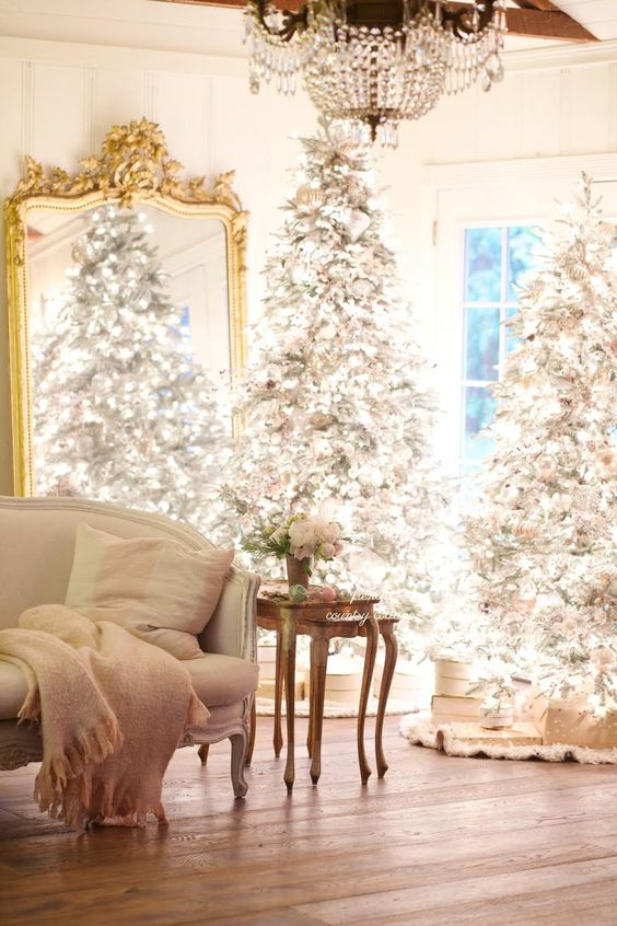 un duo di alberi di Natale affollati con molte luci e ornamenti neutri e argentati è sorprendente per uno spazio chic
