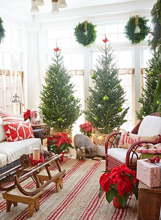 un trio di alberi di Natale posti in cesti, con ornamenti verdi e uccelli rossi in cima sembra bello