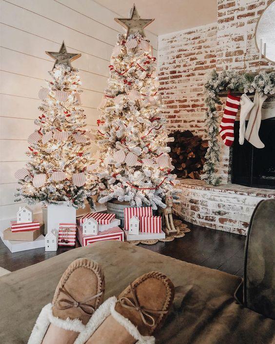 un duo di alberi di Natale affollati con luci, decorazioni a stella, zigoli di carta fa una dichiarazione di vacanza