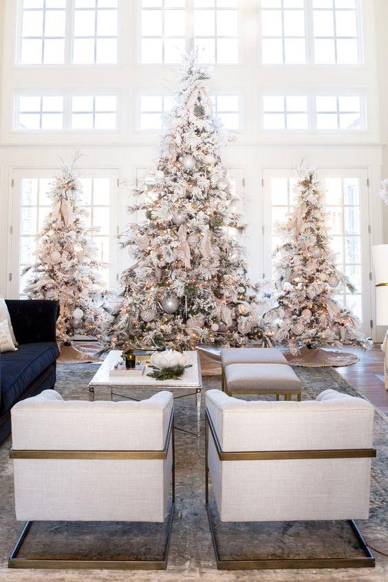 un trio di grandi alberi di Natale floccati con luci, ornamenti neutri e metallici per una favola invernale nello spazio