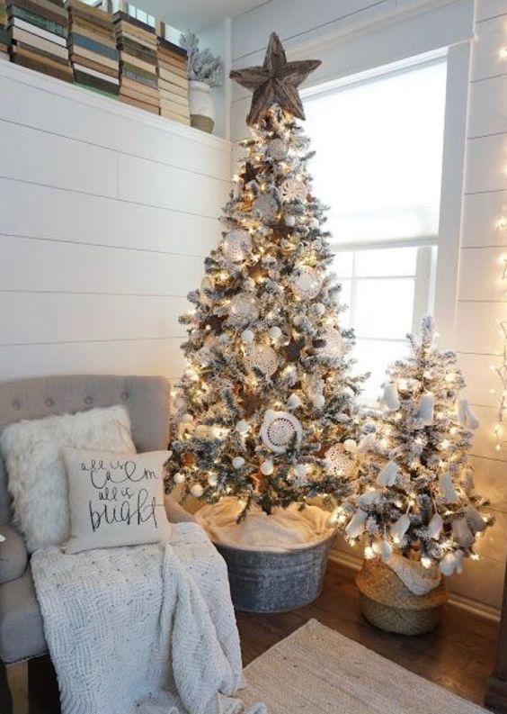 un simpatico duo di alberi di Natale affollati con luci, ornamenti bianchi e pompon per uno spazio neutro
