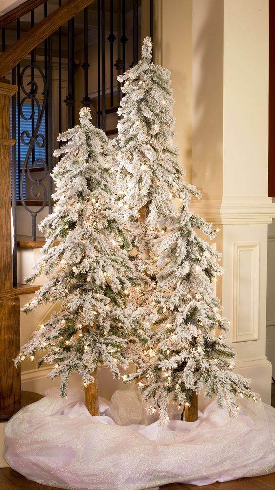 creare un paese delle meraviglie invernale con un trio di alberi di Natale floccati con luci e un po 'di tessuto bianco alla base