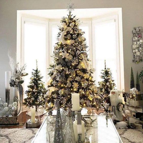 un trio di alberi di Natale eleganti e chic decorati con luci e ornamenti e piume bianchi e argento
