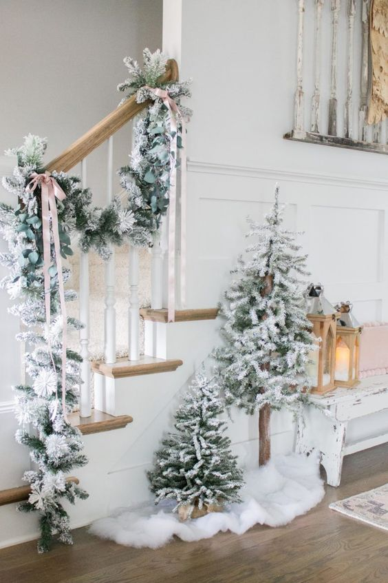due alberi di Natale floccati non decorati e una ghirlanda abbinata attaccata alla ringhiera sono un'idea meravigliosa