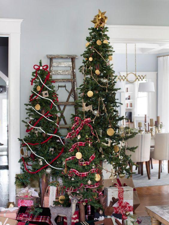 tre alberi di Natale decorati in modo stravagante con nastri placcati, rossi e bianchi, ornamenti in argilla e agrumi, oltre a topper con fiocco e stella