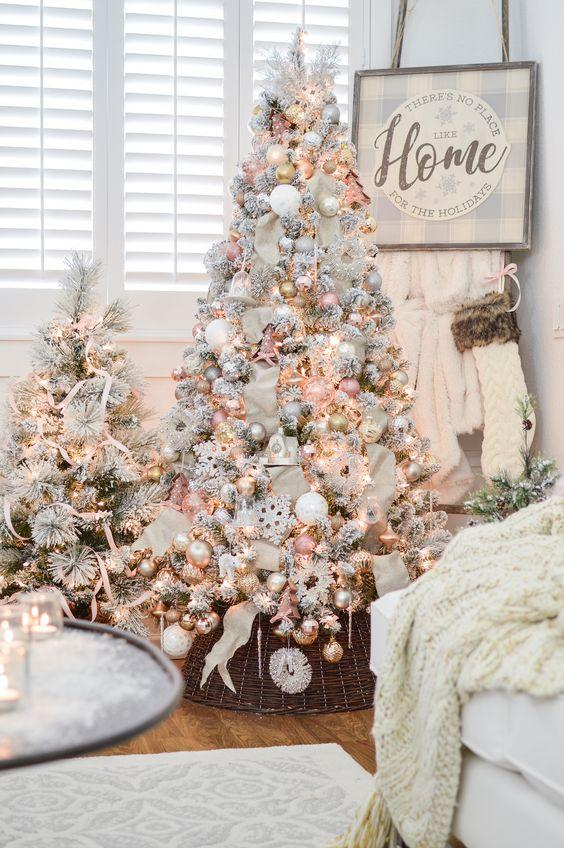 due graziosi alberi di Natale innevati con luci, decorazioni pastello e metalliche e alcune strisce per un tocco glam