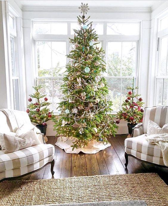 un trio di alberi di Natale, due più piccoli sono decorati con ornamenti e nastri rossi, e quello centrale è fatto in blu e verde intenso più luci