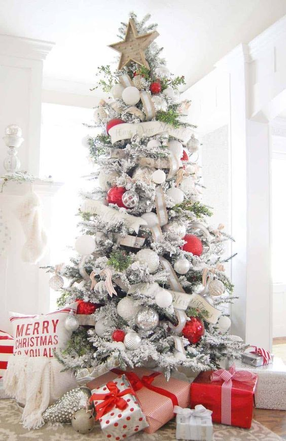 un albero di Natale floccato chic con nastri bianchi e di juta, ornamenti bianchi e metallici e quelli rossi oversize