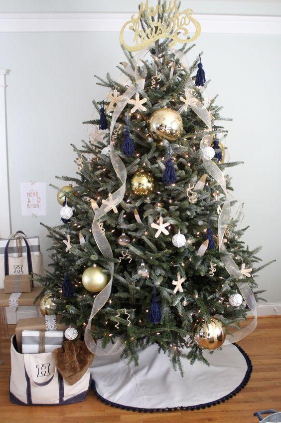 un albero di Natale da spiaggia chic con luci, nappe blu scuro, ornamenti di stelle marine, nastri e nastri metallici di grandi dimensioni e un topper calligrafico