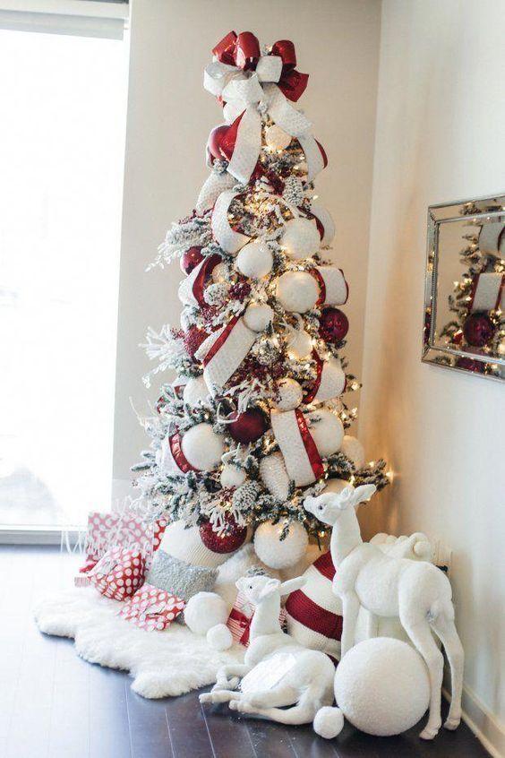 un albero di Natale floccato chic con luci, ornamenti rossi e bianchi di grandi dimensioni e nastri abbinati più un fiocco in cima