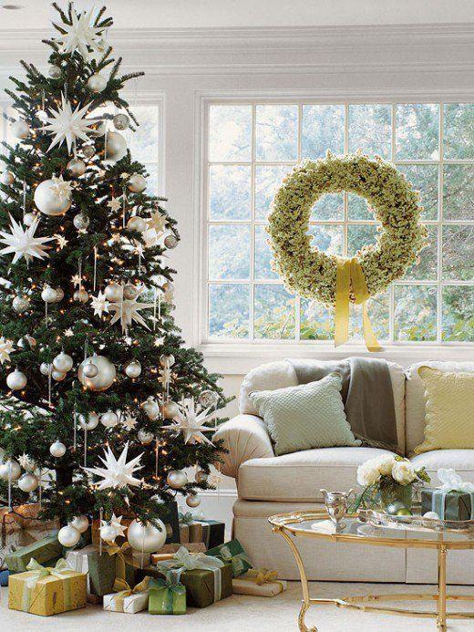 un albero di Natale decorato con luci, ornamenti perlati di varie dimensioni e ornamenti a stella, alcuni dei quali sono oversize