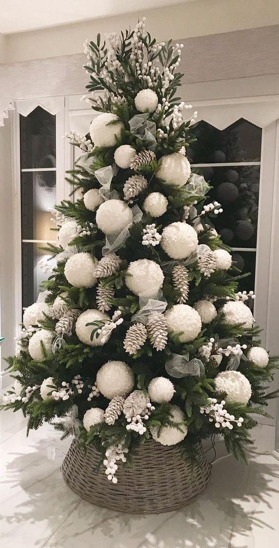 un audace albero di Natale con bacche bianche, pigne sbiancate e ornamenti di pompon bianchi oversize per un look carino