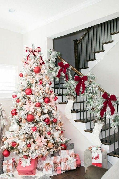 un albero di Natale floccato con luci, ornamenti rosa oversize e più piccoli metallici più fiori rosa per un look glam