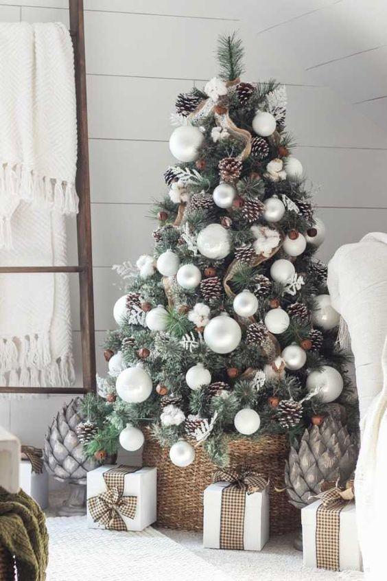 un accogliente albero di Natale da fattoria con nastri in tela di juta, pigne innevate, ornamenti perlati e cotone più un cestino