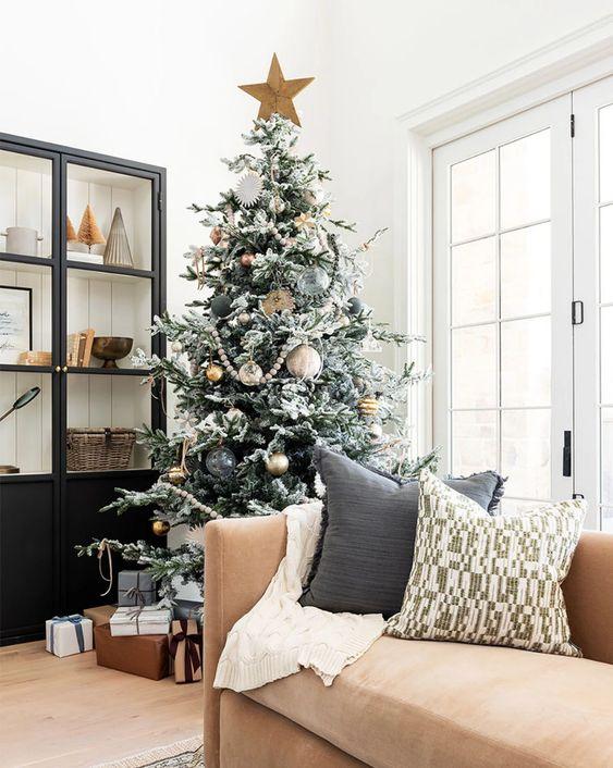 un albero di Natale floccato con ornamenti trasparenti, dorati e neri, compresi quelli di grandi dimensioni e un cappello a cilindro a stella