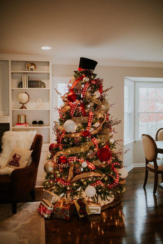 un albero di Natale decorato con luci, nastri di tela e plaid, ornamenti oversize rossi, oro e bianchi e un cappello in cima
