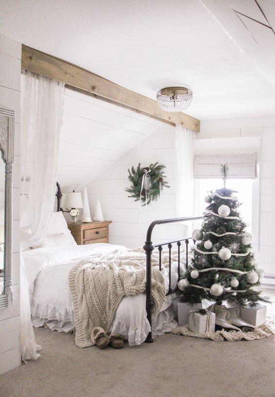 un albero di Natale decorato con nastri bianchi, fiocchi di neve d'argento e ornamenti bianchi di grandi dimensioni per uno spazio di fattoria