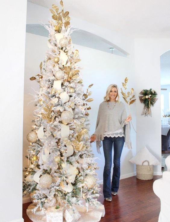un albero di Natale glam del sud con ornamenti e luci natalizie metalliche e glitterate e di grandi dimensioni più foglie dorate