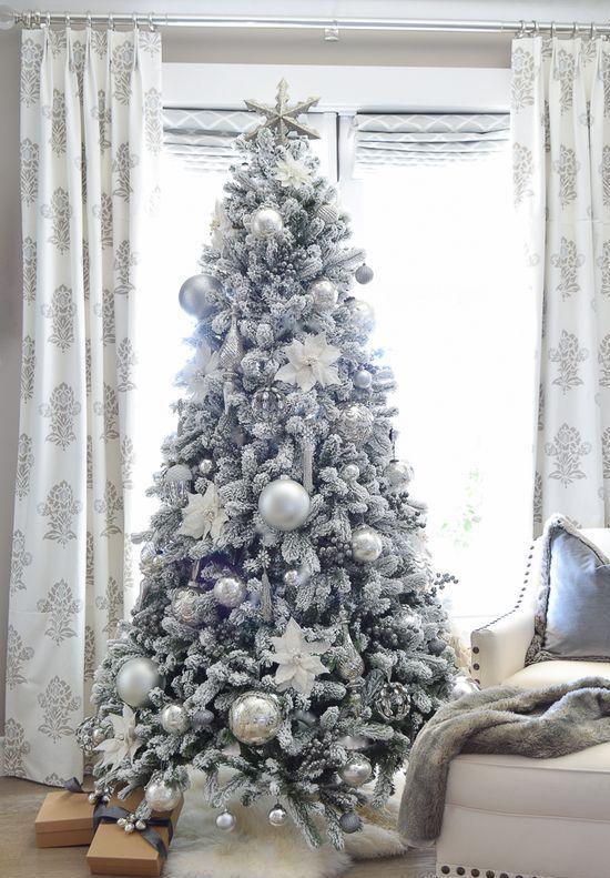 un albero di Natale floccato con glitter argento e argento soliti e ornamenti natalizi di grandi dimensioni sembra congelato