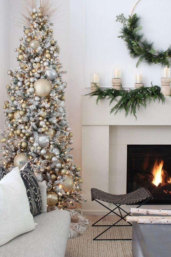 un albero di Natale super glam completamente ricoperto di ornamenti glitter oro e argento, compresi quelli di grandi dimensioni, sembra lucido