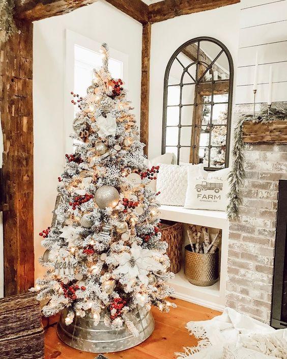 un albero di Natale di una fattoria affollato con bacche rosse, ornamenti metallici compresi quelli grandi e fiori di stoffa