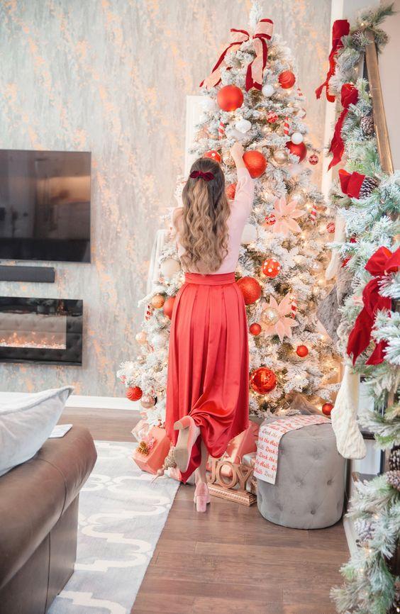 un albero di Natale glam con luci, ornamenti rossi oversize, quelli metallici e fiocchi di stoffa