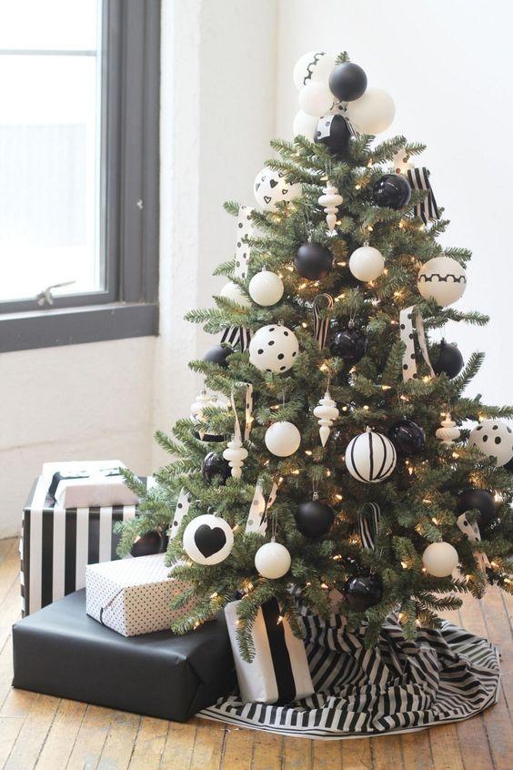 un albero di Natale moderno ed elegante con luci e ornamenti stampati in bianco e nero oversize e una gonna a righe