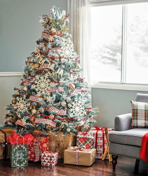 un albero di Natale rustico con nastri a quadri, ornamenti metallici e fiocchi di neve di grandi dimensioni