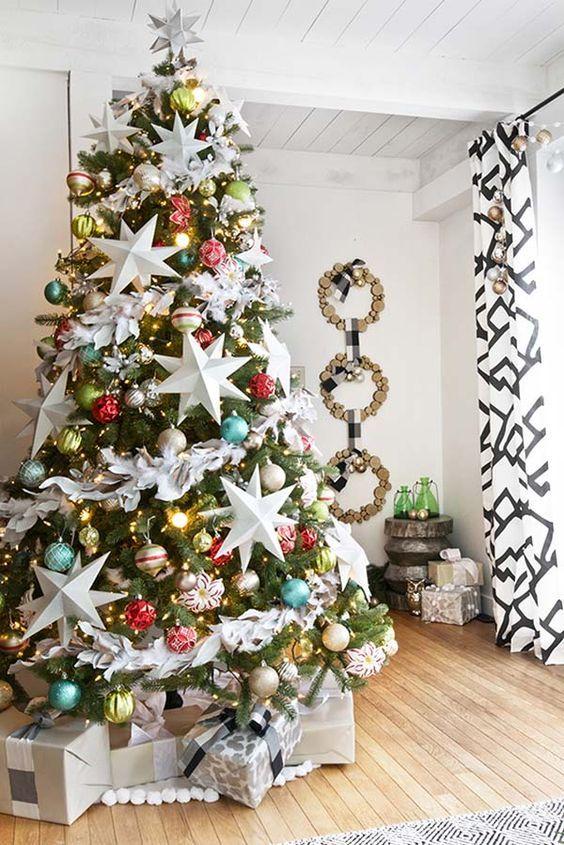 un albero di Natale luminoso con ornamenti colorati, luci e stelle bianche di grandi dimensioni sembra orecchiabile