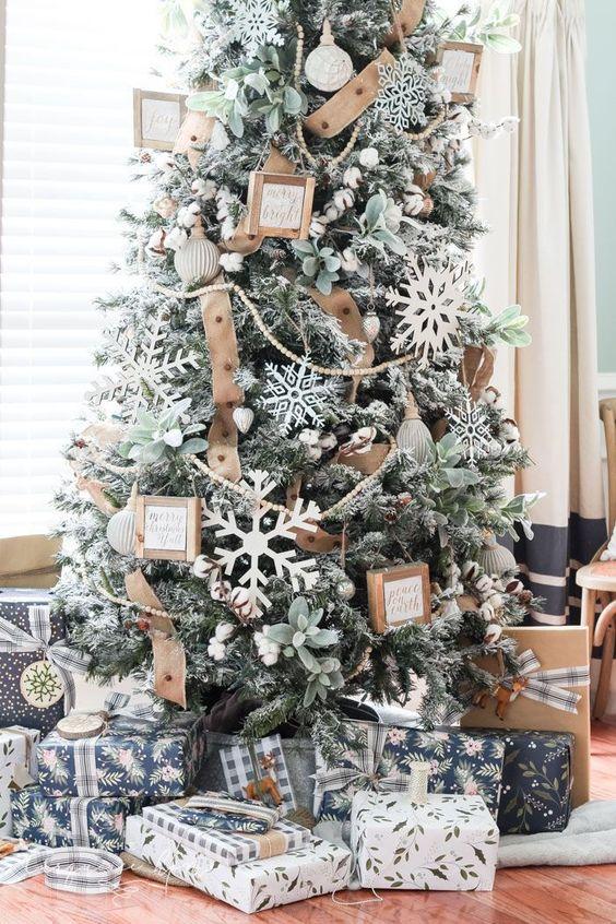 un albero di Natale floccato con ornamenti di fiocchi di neve di grandi dimensioni, nastri di juta, vegetazione e mini cornici per l'arredamento