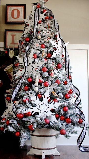 un albero di Natale floccato con nastri a quadri, ornamenti rossi e ornamenti in compensato sovradimensionati