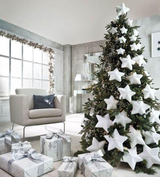 un bellissimo albero di Natale pre-illuminato decorato con stelle bianche di grandi dimensioni che scendono dall'albero