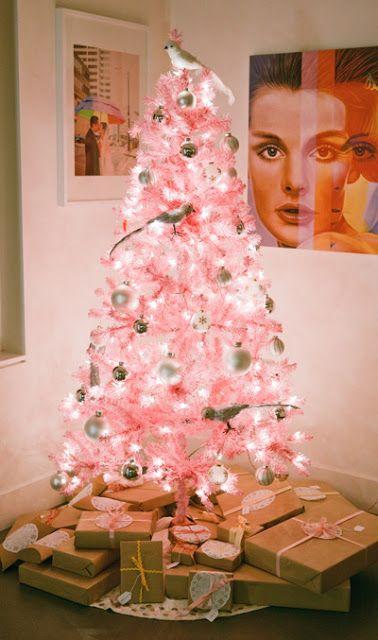 un albero di Natale rosa pastello con ornamenti bianchi e metallici e eccentrici ornamenti per uccellini e luci