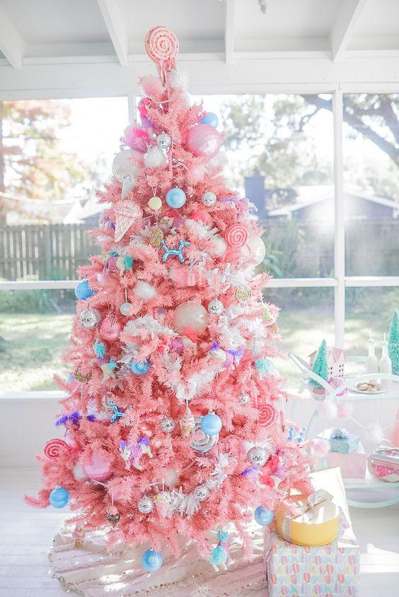 un luminoso albero di Natale color caramella con ornamenti blu audaci, ornamenti per gelato e ghiaccioli e un cappello a cilindro per caramelle
