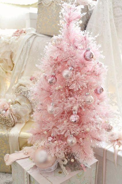 un grazioso albero di Natale rosa con ornamenti metallici lucidi che si abbinano al colore e alcune perline perlate come decorazioni