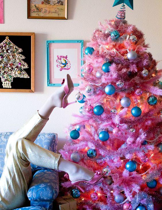 un albero di Natale rosa brillante con decorazioni e luci blu e metalliche sembra carino e retrò