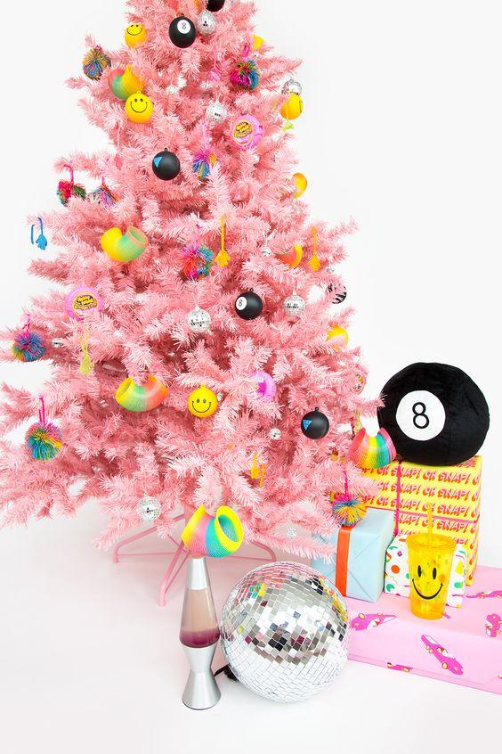 un albero di Natale rosa brillante con ornamenti moderni divertenti e colorati sembra fresco e molto audace
