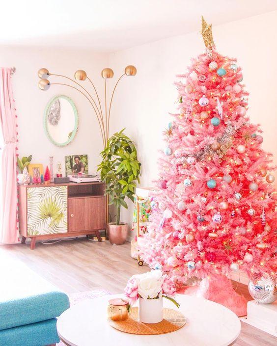 un albero di Natale rosa brillante con decorazioni pastello e metalliche e una grande stella d'oro per infondere colore al tuo spazio