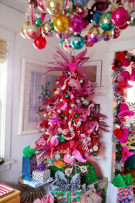 un pazzo albero di Natale rosa caldo con ornamenti metallici, verdi e rosa, fenicotteri rosa e nastri a strisce