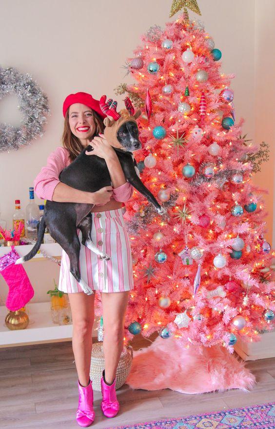un albero di Natale rosa brillante con ornamenti colorati e pastello, luci e un cappello a cilindro con stella d'oro