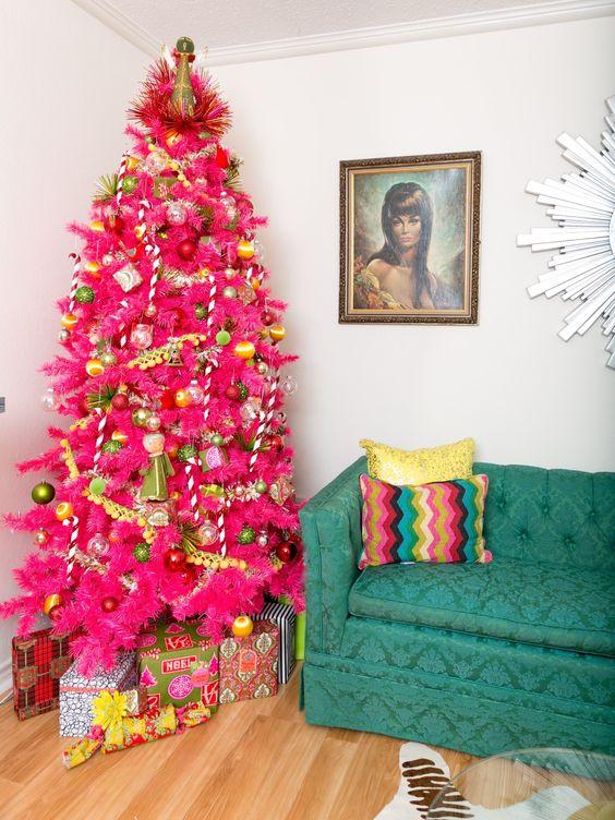 un albero di Natale rosa caldo con ornamenti verdi e dorati, ghirlande di pompon e un bizzarro cappello a cilindro
