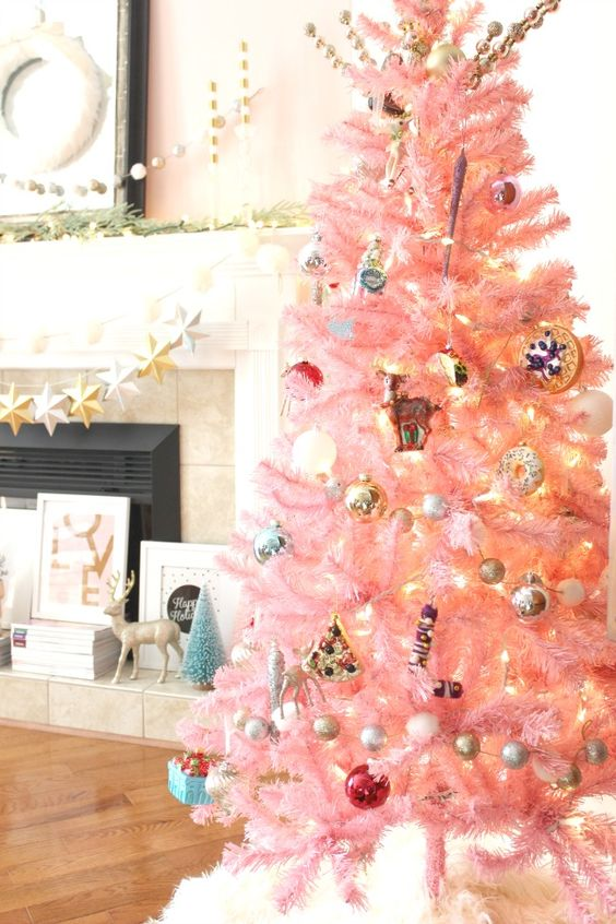 un albero di Natale rosa pastello con ornamenti metallici, luci e quelli retrò sembra un tocco di colore carino e chic