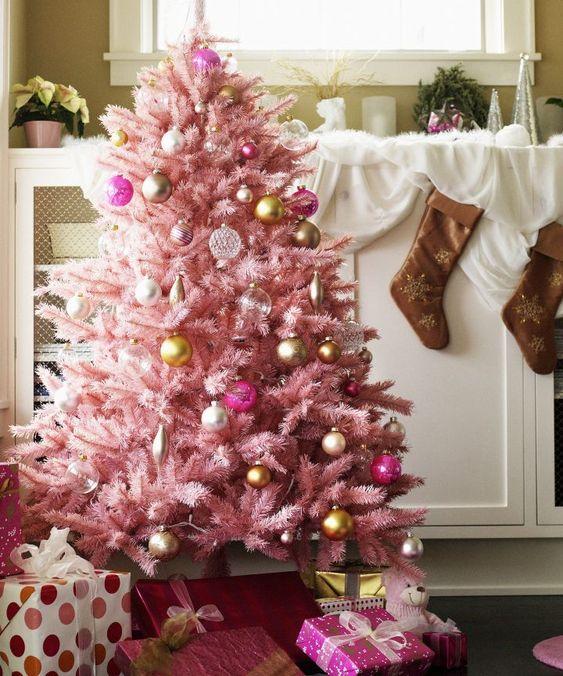 un albero di Natale rosa pastello con ornamenti trasparenti, oro e rosa con un tocco vintage sembra molto sofisticato